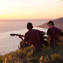 man playing guitar view sea mountain sunset singing relax musicians street photography travel UGC content